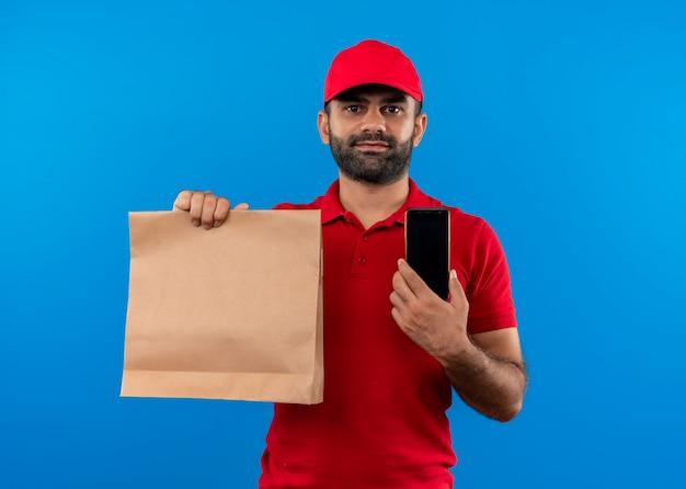 Entregador barbudo de uniforme vermelho e boné segurando um pacote de papel sorrindo, mostrando o smartphone em pé sobre uma parede azul