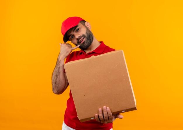 Entregador barbudo de uniforme vermelho e boné segurando uma caixa de pizza aberta, fazendo gesto de me ligar em pé sobre a parede laranja