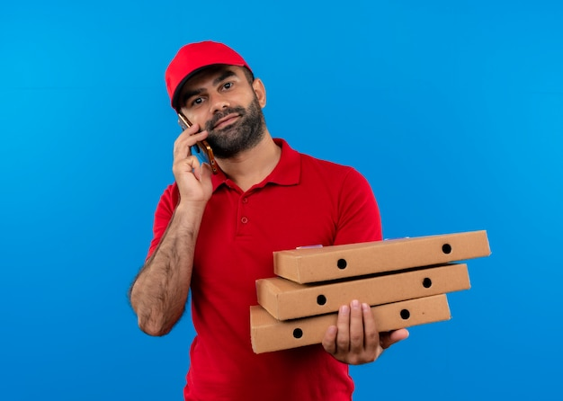 Entregador barbudo de uniforme vermelho e boné segurando uma pilha de caixas de pizza sorrindo enquanto fala no celular em pé sobre a parede azul