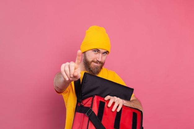 Entregador barbudo europeu abre a caixa com comida e aponta o dedo para a câmera espera sinal rosa