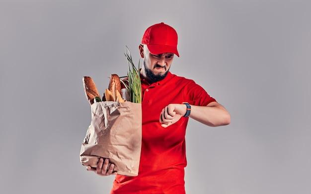 Entregador barbudo jovem com raiva descontente em uniforme vermelho segura um pacote com pão e legumes e olha para smartwatch em sua mão atrasado isolado em fundo cinza.