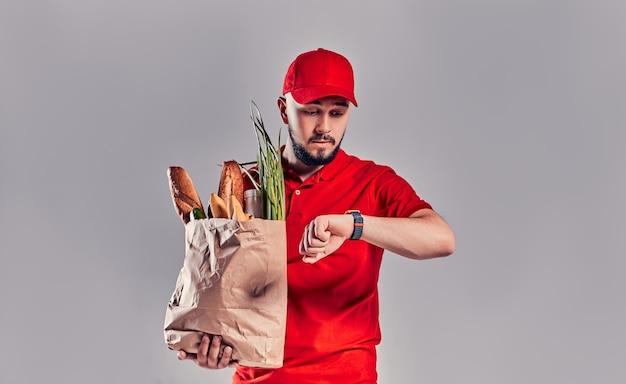Entregador barbudo jovem com um uniforme vermelho segura um pacote com pão e legumes e olha para o smartwatch em sua mão atrasado isolado em fundo cinza.