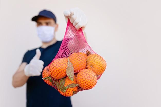 Entregador blured na máscara protetora médica e luvas com frutas de close-up laranja. mostrar sim a mão. prevenção e alimentação saudável durante uma pandemia e vírus.