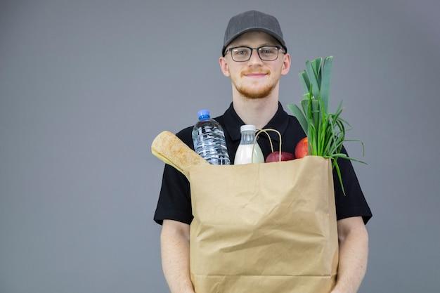 Entregador bonito em uniforme preto segurando uma sacola de papel com comida e bebida da loja