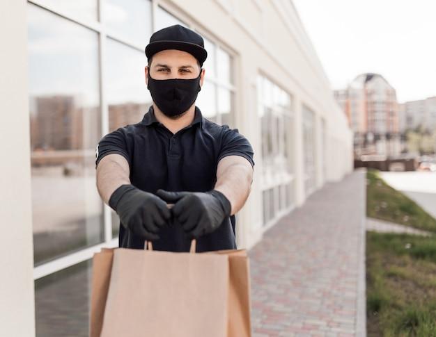 Entregador bonito uniforme preto com sacos