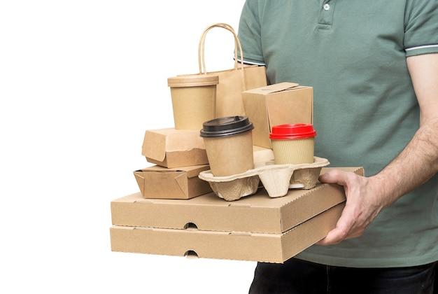 Entregador carrega diversos recipientes de comida para viagem, caixa de pizza, xícaras de café no suporte e saco de papel isolado no fundo branco