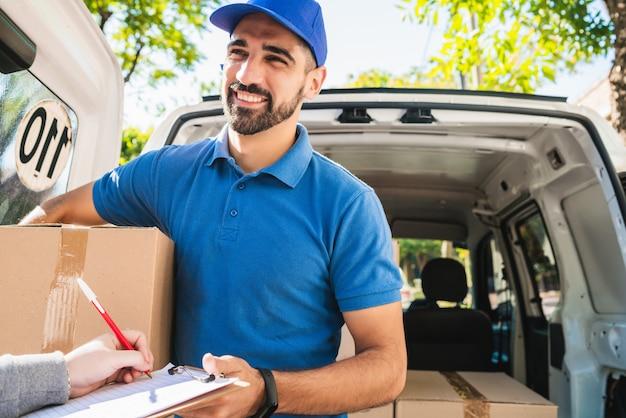Entregador carregando pacote enquanto cliente assinar na área de transferência.