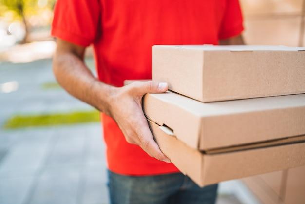 Entregador carregando pacotes ao fazer entrega em domicílio.