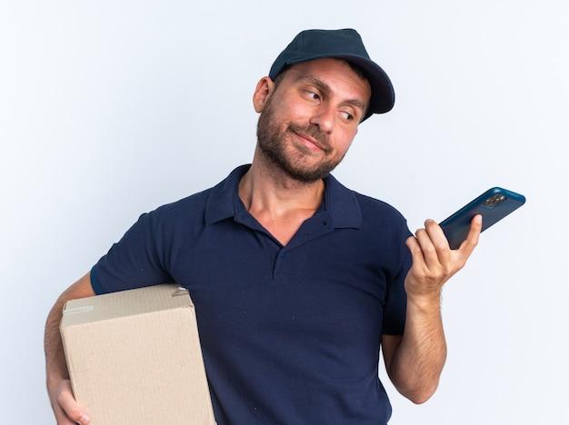 Entregador caucasiano jovem sem noção de uniforme azul e boné segurando uma caixa de papelão e um celular olhando para o celular