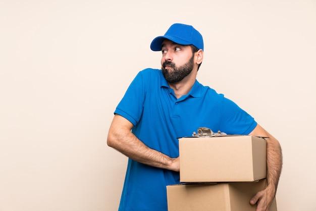 Entregador com barba fazendo dúvidas gesto enquanto levantando os ombros