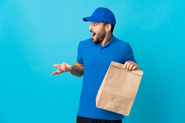 Entregador com barba isolada em azul com expressão facial surpresa