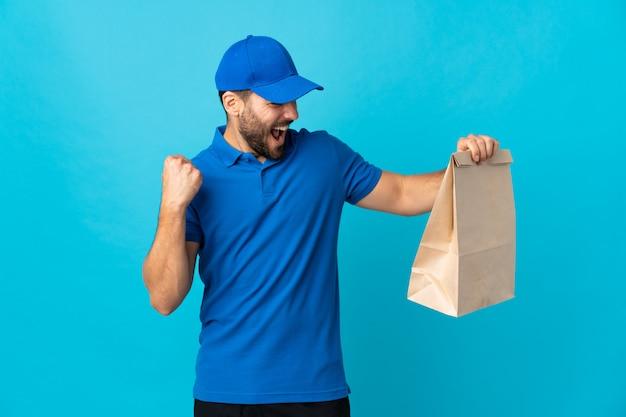 Entregador com barba isolada em azul comemorando uma vitória