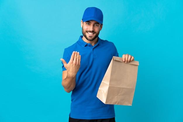 Entregador com barba isolada em azul convidando para vir com a mão.