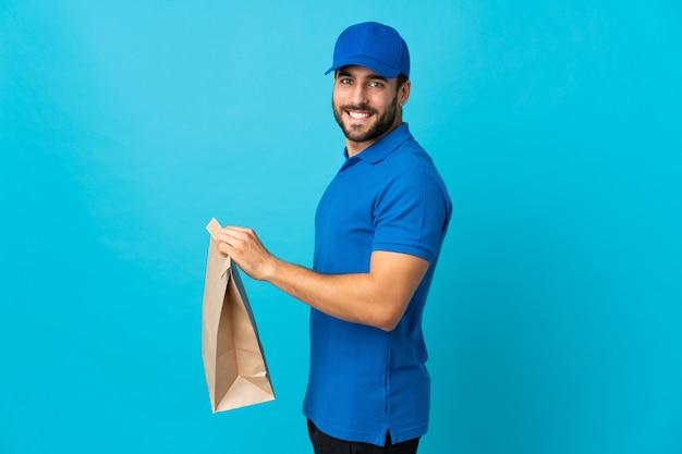 Entregador com barba isolada em azul, sorrindo muito