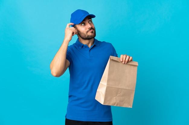 Entregador com barba isolada em azul, tendo dúvidas e com a expressão do rosto confuso
