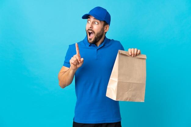 Entregador com barba isolada em fundo azul com a intenção de perceber a solução enquanto levanta um dedo