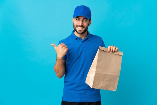Entregador com barba isolada na parede azul, apontando para o lado para apresentar um produto