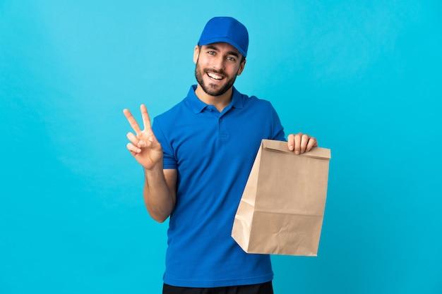 Entregador com barba isolada na parede azul, sorrindo e mostrando sinal de vitória