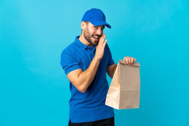 Entregador com barba isolada na parede azul sussurrando algo