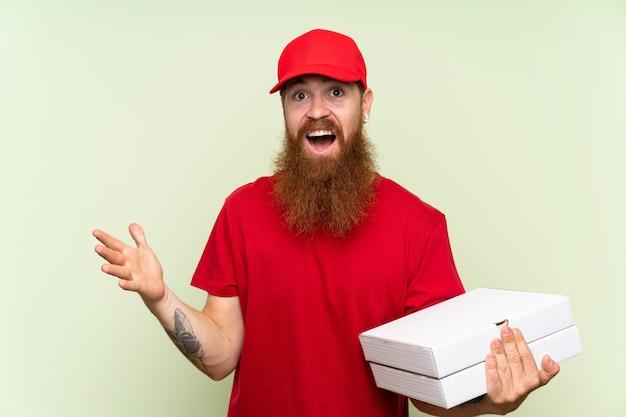 Entregador com barba longa isolado parede verde com expressão facial chocado