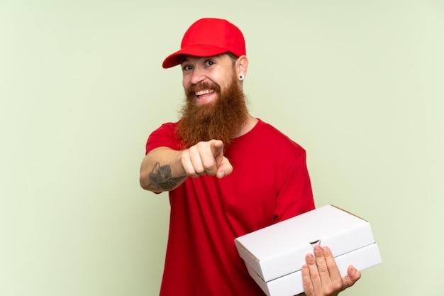 Entregador com barba longa sobre parede verde isolada aponta o dedo para você com uma expressão confiante