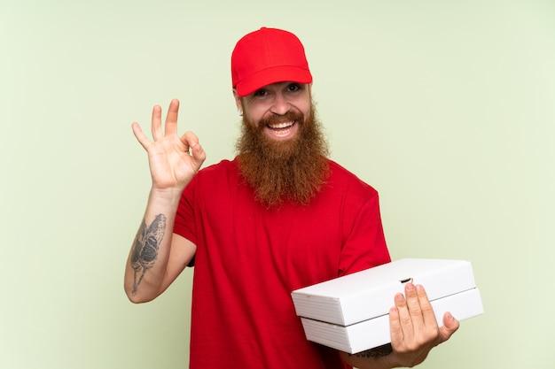 Entregador com barba longa sobre parede verde isolada, mostrando sinal de ok com os dedos