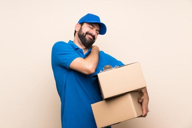 Entregador com barba sobre isolado, sofrendo de dor no ombro por ter feito um esforço