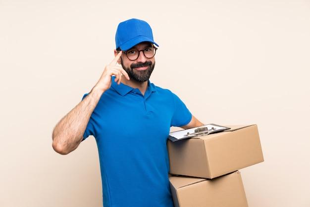 Entregador com barba sobre parede isolada com óculos e sorrindo