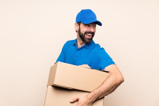 Entregador com barba sobre parede isolada com os braços cruzados e feliz
