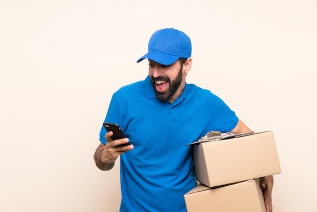 Entregador com barba sobre parede isolada com telefone em posição de vitória