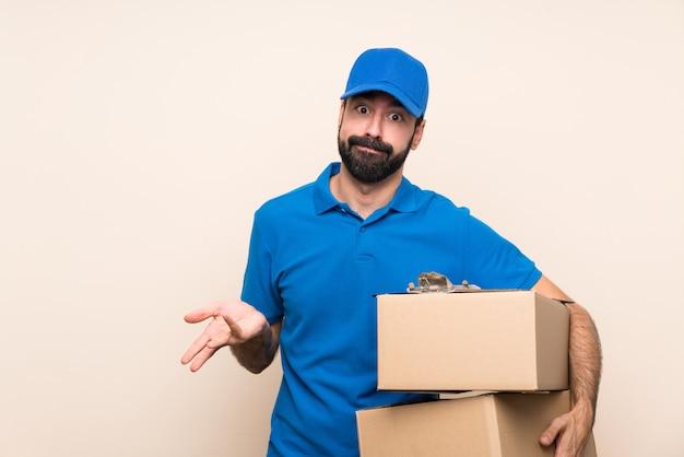Entregador com barba sobre parede isolada, fazendo o gesto de dúvidas