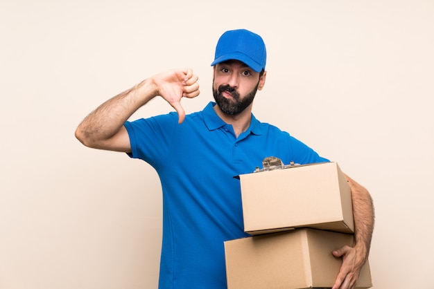 Entregador com barba sobre parede isolada, mostrando o polegar para baixo