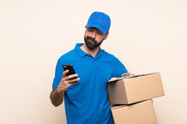 Entregador com barba sobre pensamento isolado e enviar uma mensagem