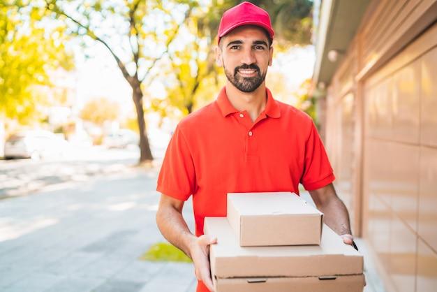 Entregador com caixa de pizza ao ar livre.