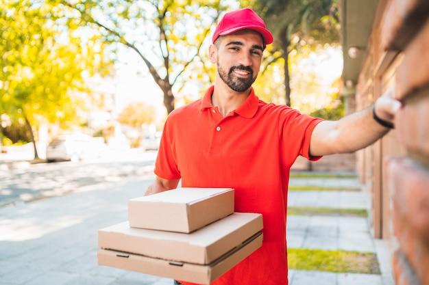 Entregador com caixa de pizza tocando a campainha da casa