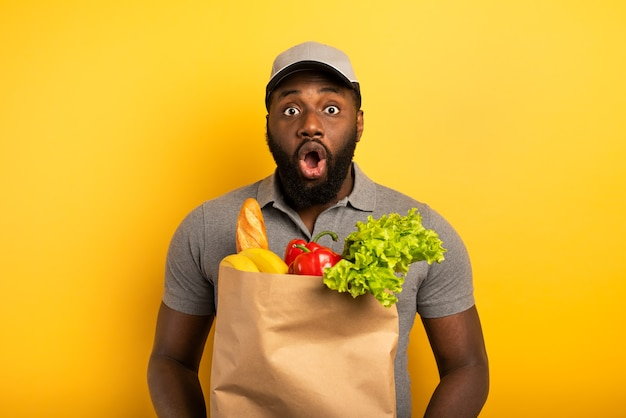 Entregador com expressão maravilhada pronto para entregar a sacola com comida