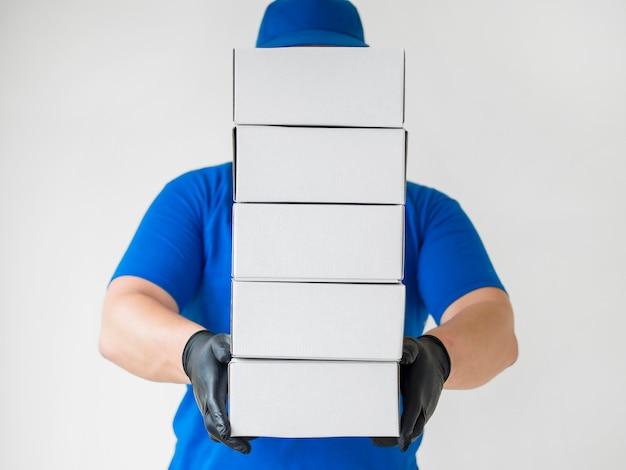 Entregador com luvas segurando caixas