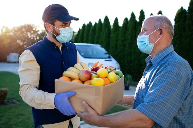 Entregador com máscara de proteção entregando comida para um homem idoso durante a pandemia covid19
