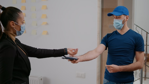Entregador com máscara de proteção facial e luvas, entregando caixa de comida para viagem durante a hora do almoço no escritório da empresa