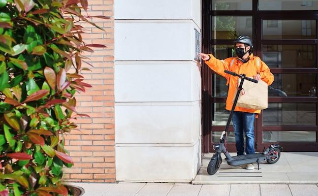 Entregador com máscara facial e scooter elétrica toca a campainha para entregar um pacote