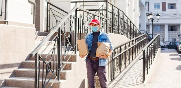 Entregador com máscara protetora perto da casa do cliente, ao ar livre