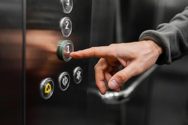 Entregador com pacote no elevador close-up