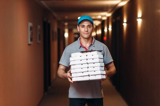 Entregador com pizza fresca em caixas de papelão