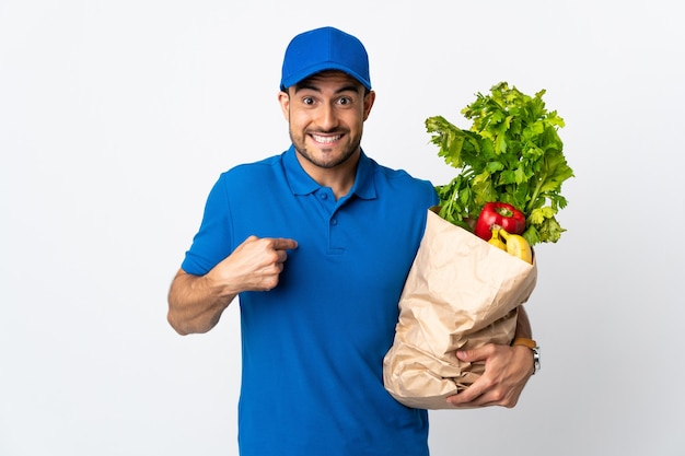 Entregador com vegetais isolados no branco com expressão facial surpresa