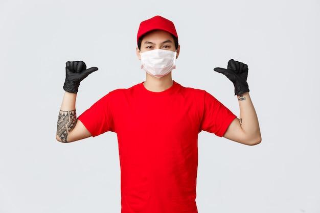 Entregador confiante apontando-se, a empresa pode fazê-lo. correio entusiástico de uniforme vermelho, máscara médica e luvas protetoras se exibindo, pedindo para confiar nele, use serviço de entrega segura