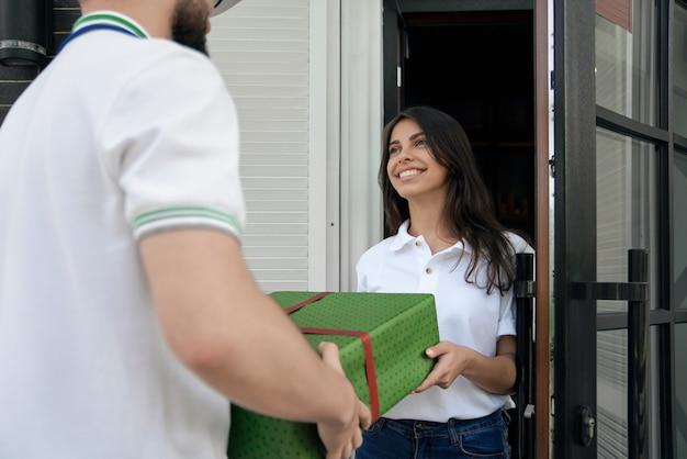 Entregador dando caixa de presente para mulher