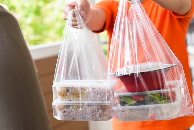 Entregador dando lancheira refeição nos sacos para cutomer que encomendou on-line em casa