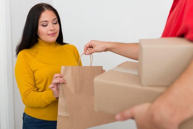 Entregador dando uma sacola de compras para uma mulher
