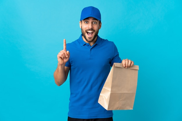 Entregador de barba isolado na parede azul apontando para cima uma ótima idéia