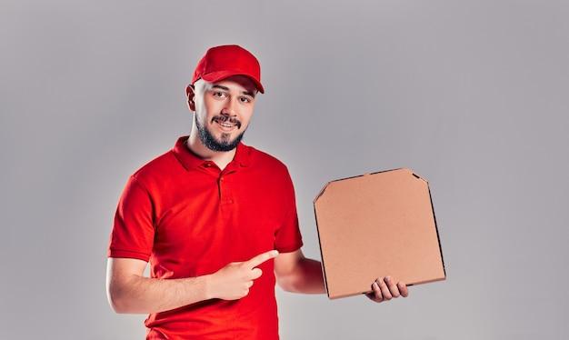 Entregador de boné vermelho, t-shirt dando comida pedir pizza caixas isoladas em fundo cinza. mensageiro de pizzaiolo empregado masculino segurando pizza no espaço vazio de cópia plana de papelão em branco. conceito de serviço